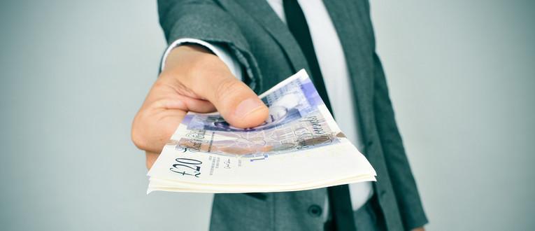 Man in Suit Handing Over GBP Banknotes
