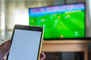 Smartphone Held In Front of Television Showing Football