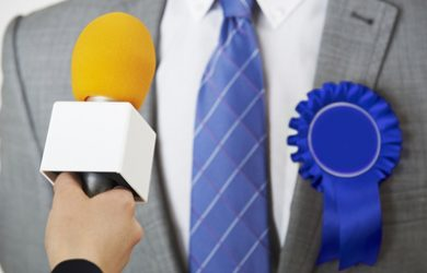Politician with Blue Rosette Being Interviewed