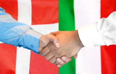 Handshake In Front of Denmark and Italy Flags