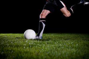 Footballer Kicking Ball Against a Dark Background