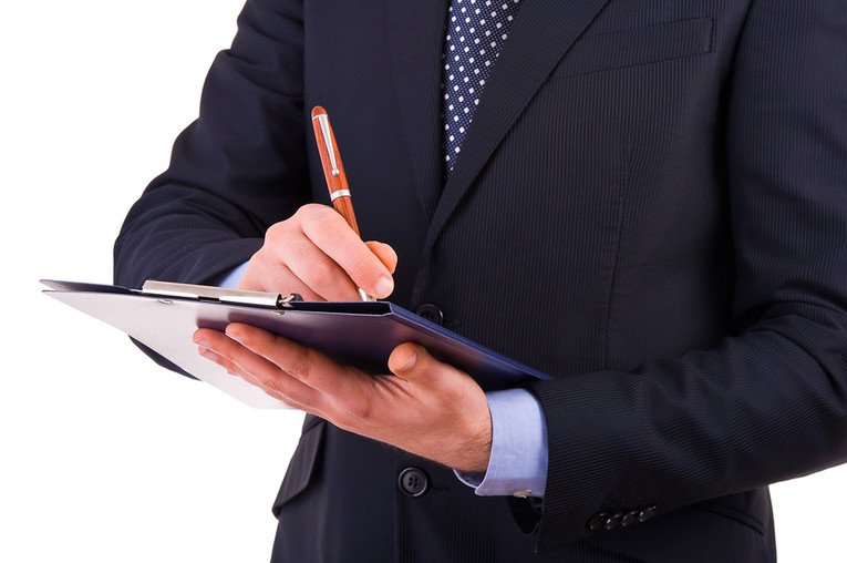Businessman Making Notes on a Clipboard