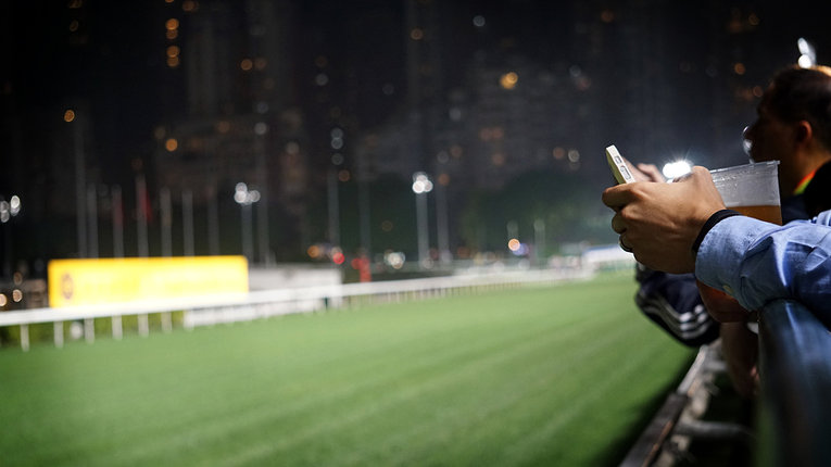 Man Betting on Phone at Horse Race