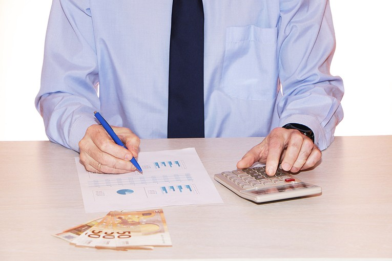 Businessman Looking at Figures with Euros on Desk