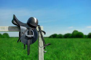 Saddle Hanging on Fence