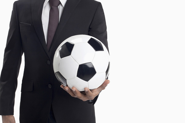 Man in Suit Holding Out Football