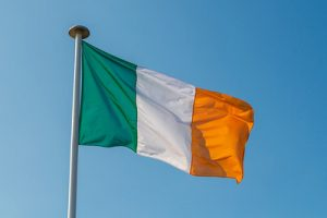 Irish Flag Waving Against Blue Sky