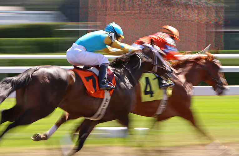 Two Blurred Horses Racing on Dirt